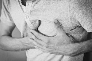 fekete-fehér fotó - az ember a mellkasát tartja magas vérnyomás