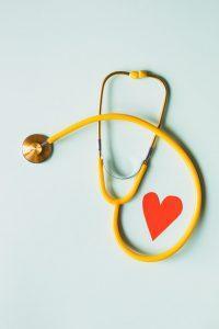 sárga sztetoszkóp, papír szívvel, zöld háttérrel