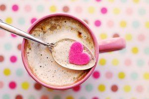 ital egy rózsaszín bögrében egy kanállal, amelyen a szív fekszik, színes háttérrel